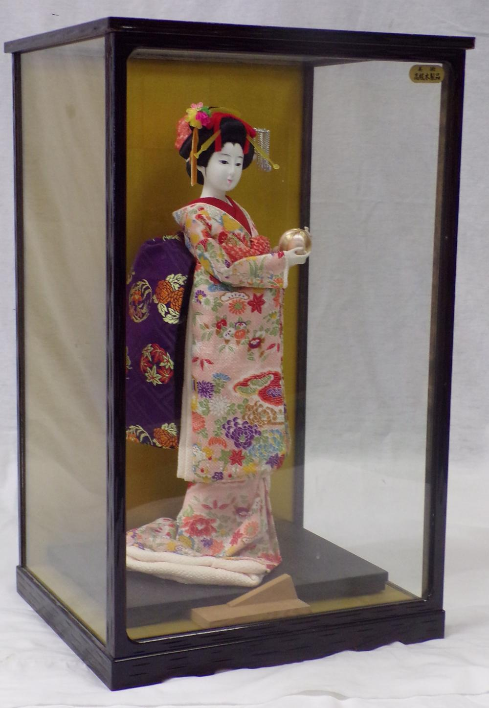 Japanese Geisha Girl figure together with a wood & glass display case, 16'' T; case 21'' T x 13''W x 11 ½''D.
