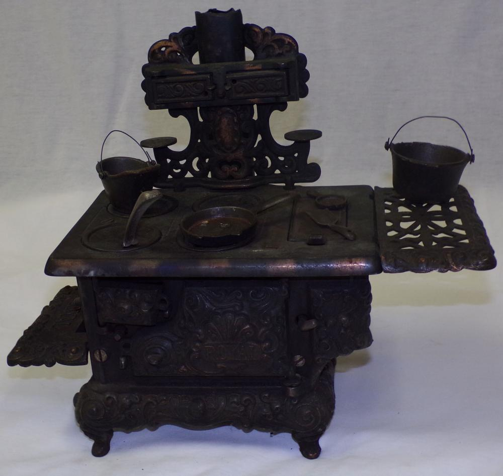 Vintage doll size cast iron wood stove by Royal with back & side attachments, having pots and pans, stove lifter, etc., marked on back of case Kenton Brand,