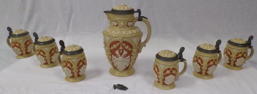 German pottery beer stein set in cream, rust/orange & ivory colors having a raised figural & coat of arms design, lid & thumb grips in pewter, marked Villeroy & Bach Mettlach, Made in Germany,#2076, pitcher thumb grip needs repair