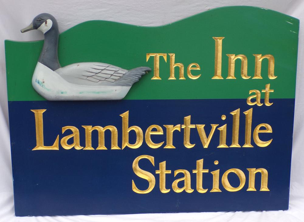 "Wooden 1 sided advertising sign, The Inn At Lambertville Station, painted green & blue with gold lettering with duck's head & body in upper left had corner, 35"" T x 48"" W x 3 ¾"" D"