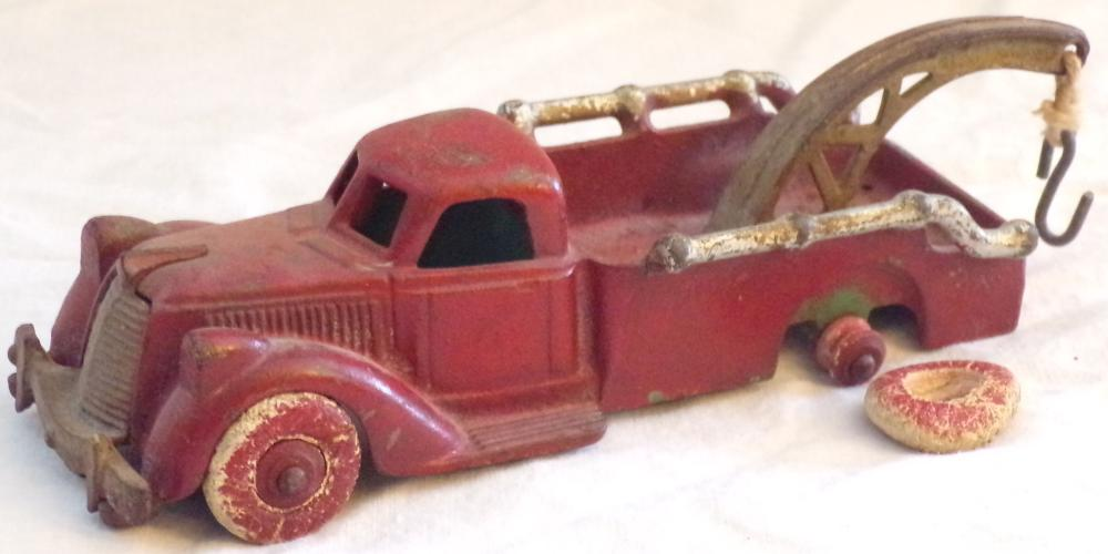 "Vintage cast iron toy truck painted red and silver, painted green underneath, marked Hubley USA, 3235, paint scratched and scuffed throughout, needs replacement tires, tow hook probably not original, approx. 2"" T x6 ¾"" L x 2 ½"" W"