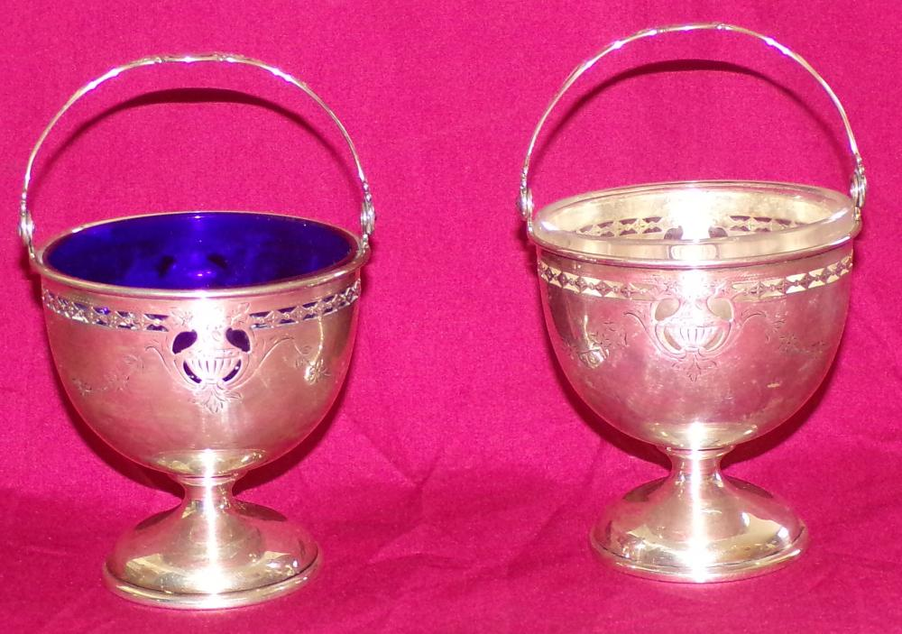 "Pair of matching sterling silver basket form sugar bowls with swing handles & reticulated urn form design with  engraved flowers marked Black, Starr & Frost Exclusive Design, #122/5433, 1 with cobalt blue glass insert, the  other with clear glass insert, monogrammed, each 3 ½"" T (without handle) x 3 ½"" top diameter"