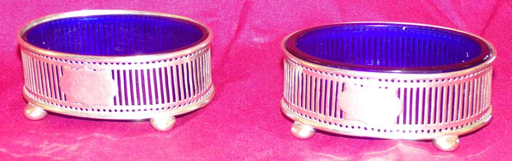 "Pair of oval sterling silver master salt cellars, vertical reticulated slat form design on footed bases, each with cobalt  blue glass inserts, #948, monogrammed, each 1 ¼"" T x 3 ¼"" W x 2 ¼"" D"