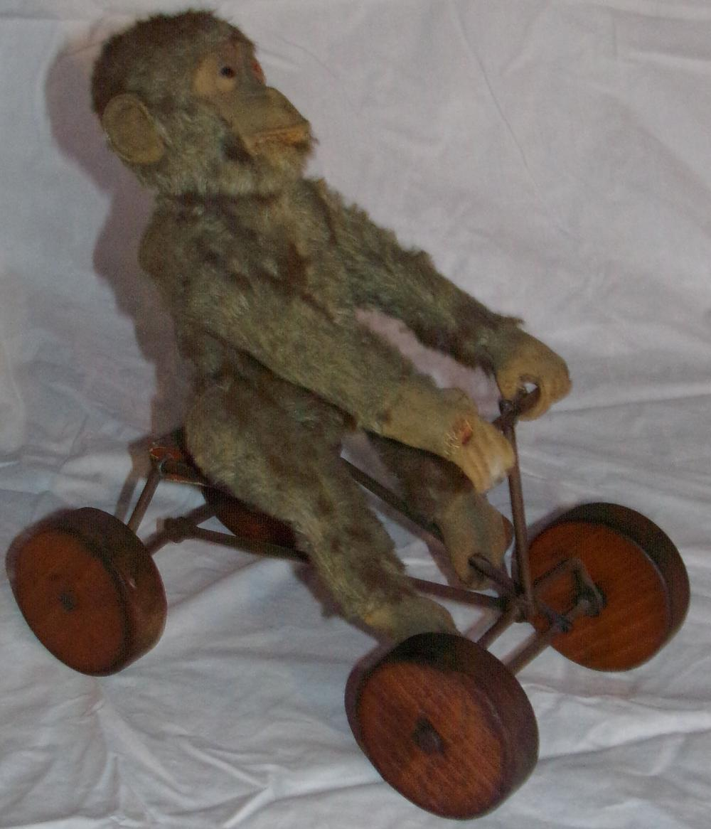 "Stuffed toy jointed monkey riding on a metal cart with four wooden wheels, wheels are marked Steiff, Made in  Germany, some covering on hand & body partially missing, original unrestored condition, 101/4"" T x 5 ¼"" W x  9"" L, wheels each 2 ½"" diameter"