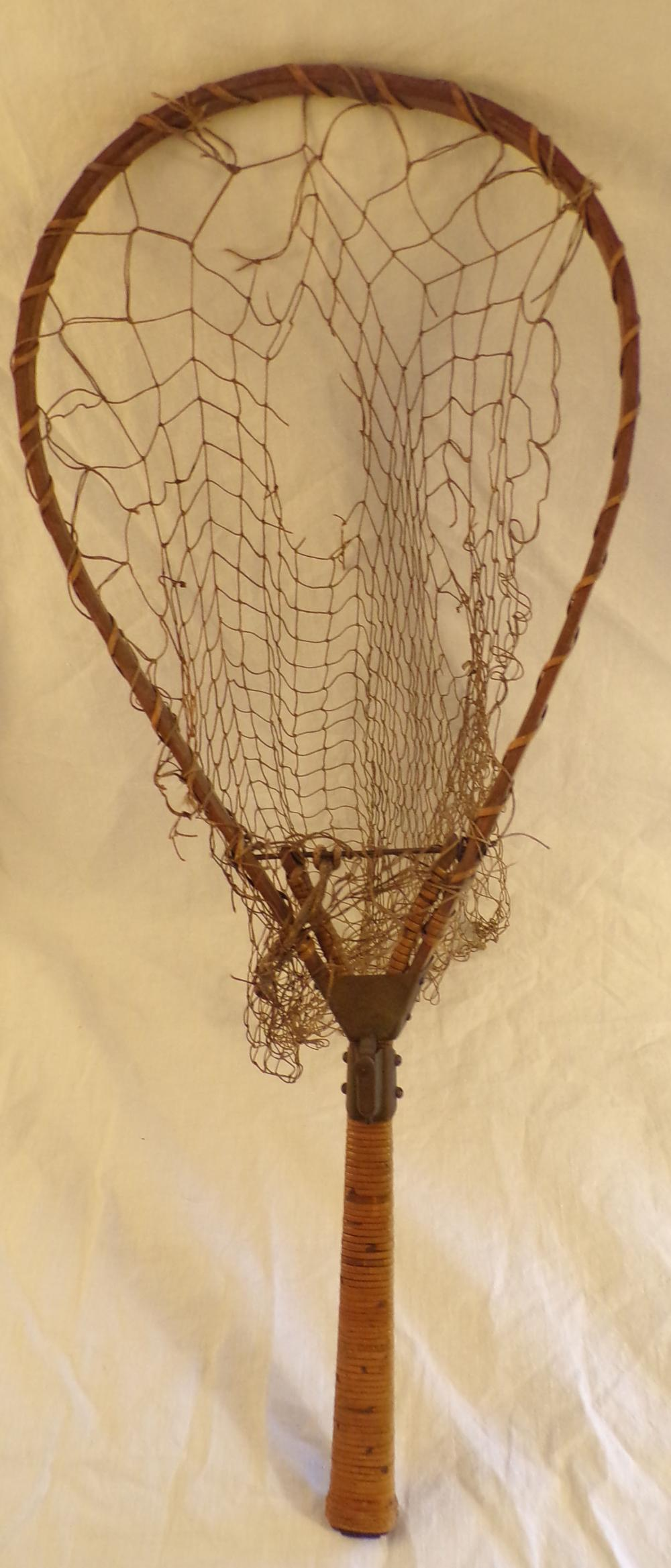 "Vintage bentwood fishing net with wicker/reed work handle marked The Barnes, No. 939381, having a folding  handle with thumb latch, original netting is damaged and needs to be restrung, 24 ½"" L x 10"" W"