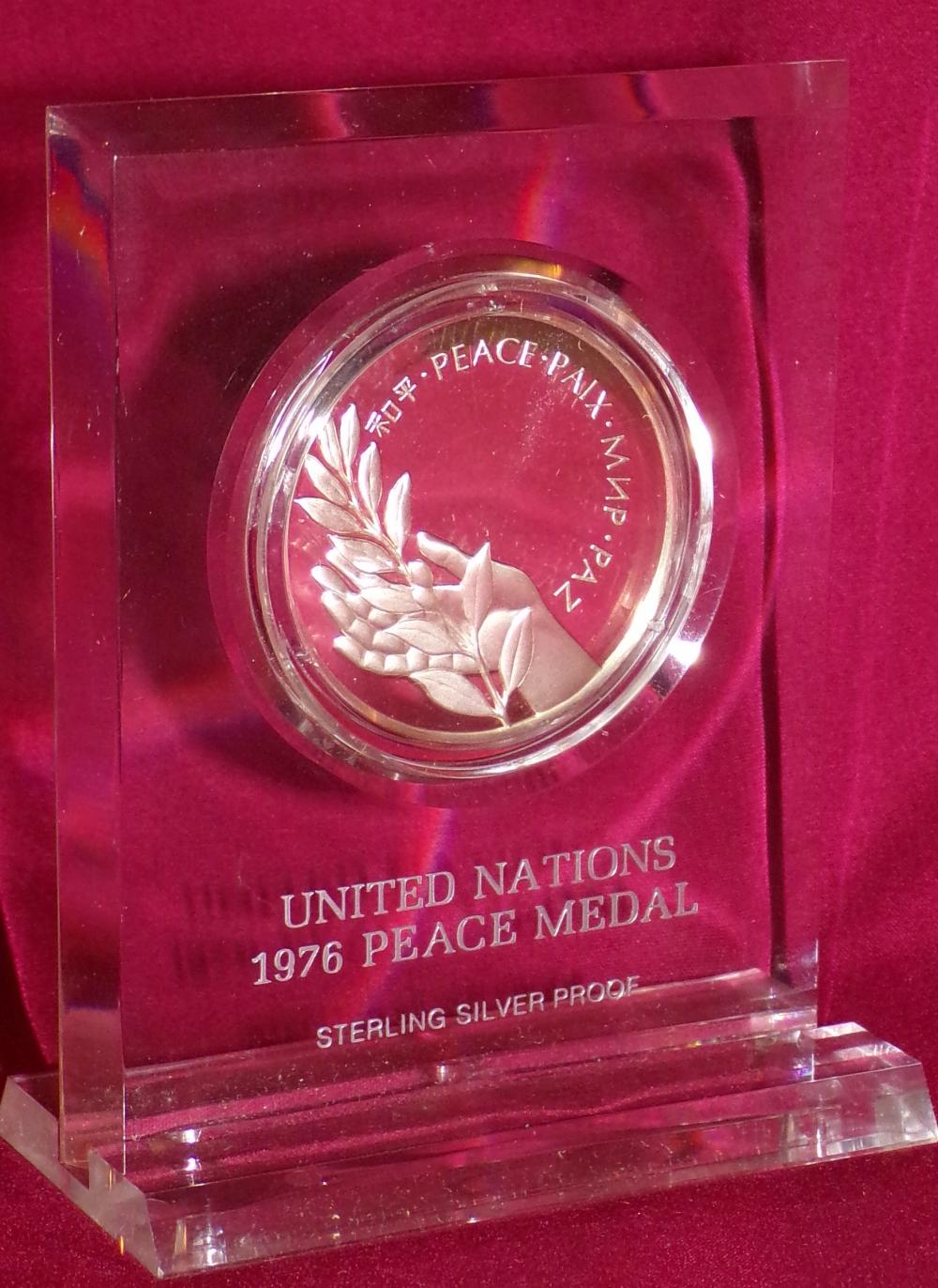 "Sterling silver proof commemorative United Nations 1976 Peace Medal mounted in a custom made clear  plastic stand, stand – 3 ¾"" T x 3"" W, medal – 1 5/8"" diameter"