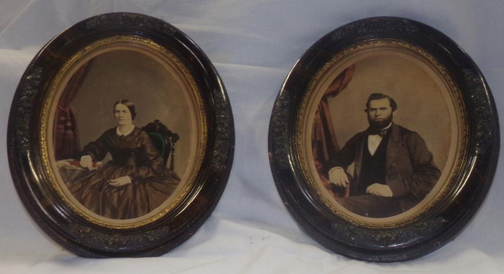 Pair of color portrait photographs with matching oval Victorian frames, scenes of a man & woman in seated positions,