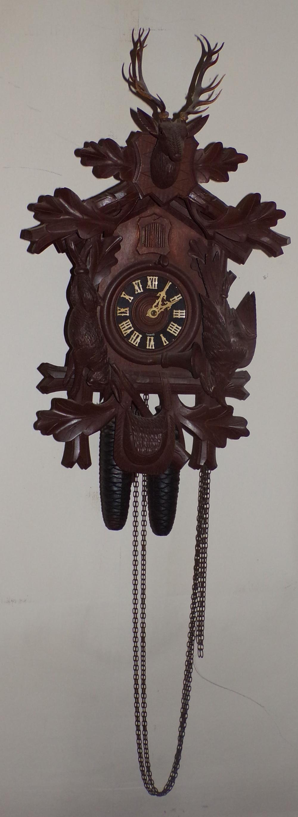"Cuckoo clock marked Germany with buck, rabbit and bird carvings, horn gun & saddle bag carving at base,  pineapple form weights & leaf form pendulum, approx. 22 ¾"" T x 14"" w x 10 ¾"" D"
