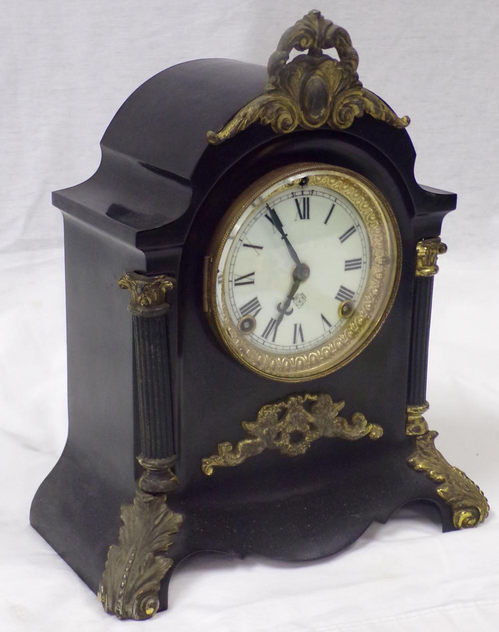 Ansonia shelf clock in black metal case having brass plated ornamental decoration