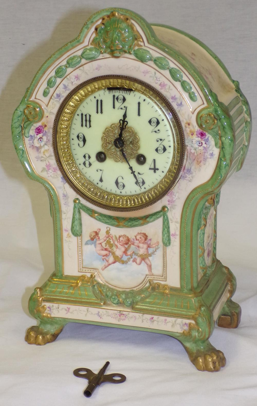 China clock decorated in ivory & green, decorated with cherubs & floral design, dome top ending in paw feet,  French movement, no maker indicated, no pendulum