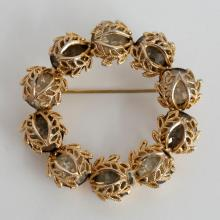 Gold plated round brooch pin with smokey quartz color rhinestones