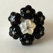 Sterling silver rhodium plated ring with carved black onyx and white mother of pearl flowers and bezel set CZ