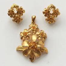 Gold plated set of flower shape post and omega clasp earrings with matching pendant satin and shiny finish