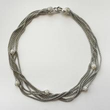 Silver tone multichannel necklace with fancy clasp and round beads with white rhinestones