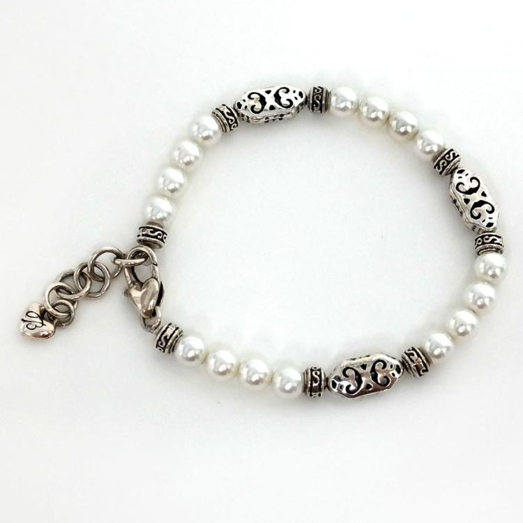Silver tone bracelet with 6 mm white round faux pearls and antique finish spacers and links, signed by symbol for company BRIGHTON
