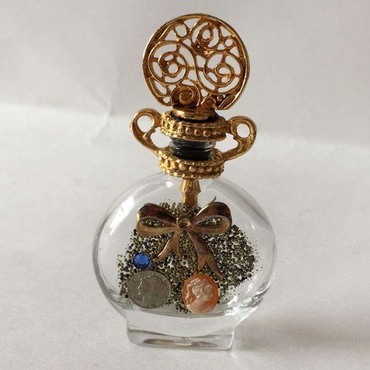 Vintage small flat glass bottle embellished from one side with gold plated top for soap bubbles liquid