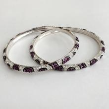 Pair of silver tone bangle bracelets with purple and white rhinestones