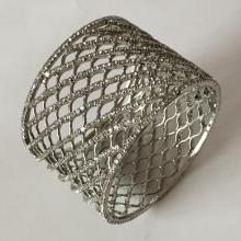 Silver tone bangle bracelet with prongs set white rhinestones all around