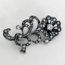 Blackened metal brooch pin in shape FLOWER with prongs and bezel set CZs