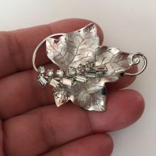 GA: Sterling silver textured and rhodium plated LEAF shaped brooch pendant with prongs set white rhinestones, signed