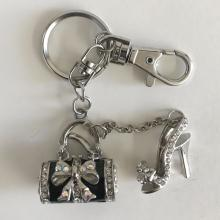Silver tone key chain with dangling high hill shoe and handbag charms with white rhinestones