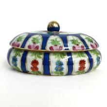 Oval shape porcelain dish with lid embellished with multicolor enamel and gold tone lines