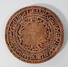 A Spanish circular wooden plaque, carved to the