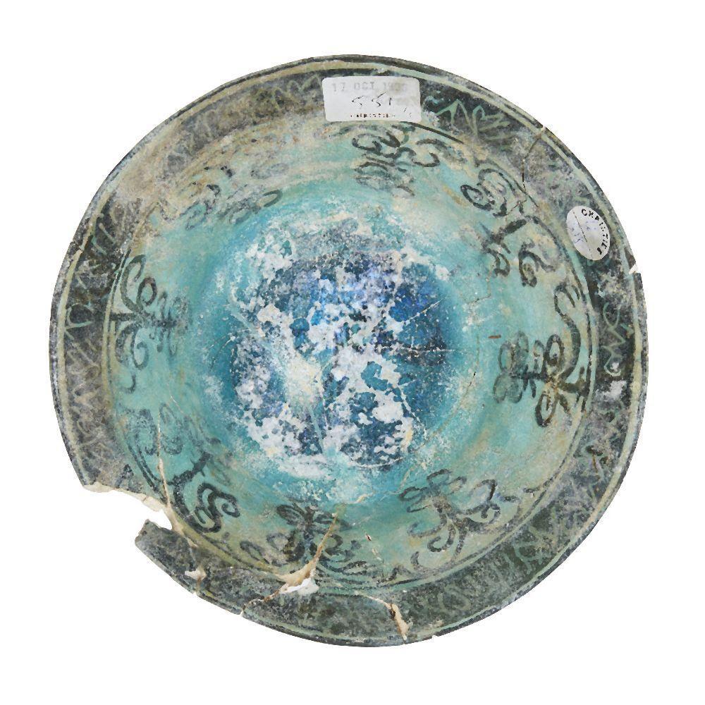 A damaged Kashan turquoise-glazed pottery bowl, Iran, 12th century, painted