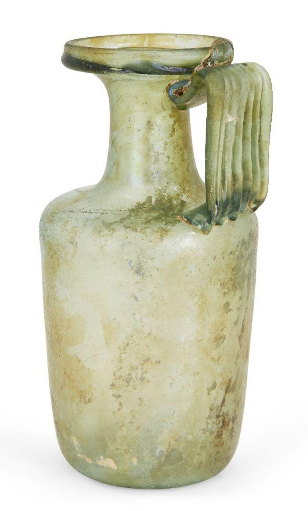 A Roman green glass flask, 1st-3rd century AD, on an indented base, rounded