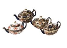A pair of  Royal Crown Derby miniature teapots and covers