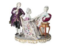 A Sitzendorf figure group of two ladies at leisure with an attendant admirer