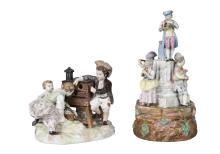 A Berlin KPM porcelain figure group of a boy helping two girls in front of a magic lantern show