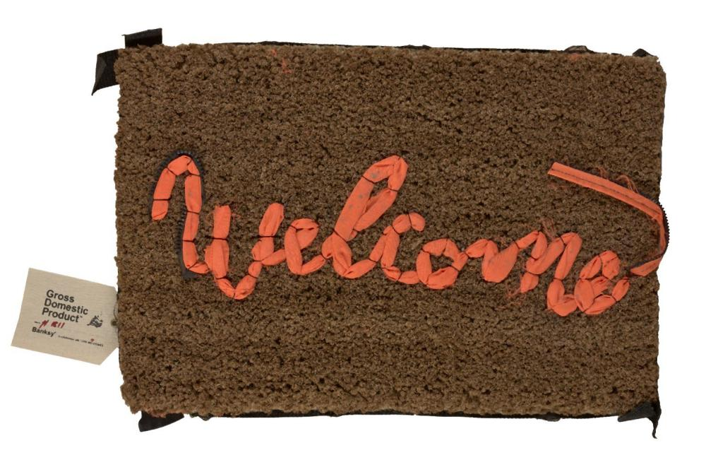 Banksy, British b.1974- Welcome Mat, 2020; hand-stitched mat, in fabric repurposed from life ve