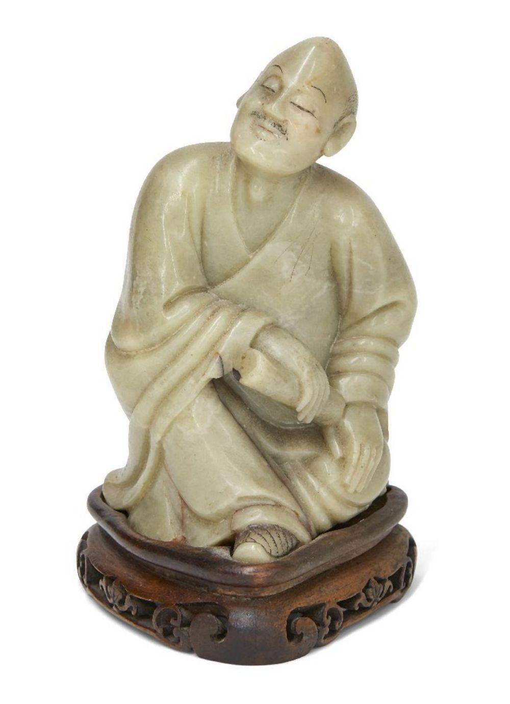 A Chinese soapstone carving of Luohan, 19th century, carved in a relaxed seated position with long f