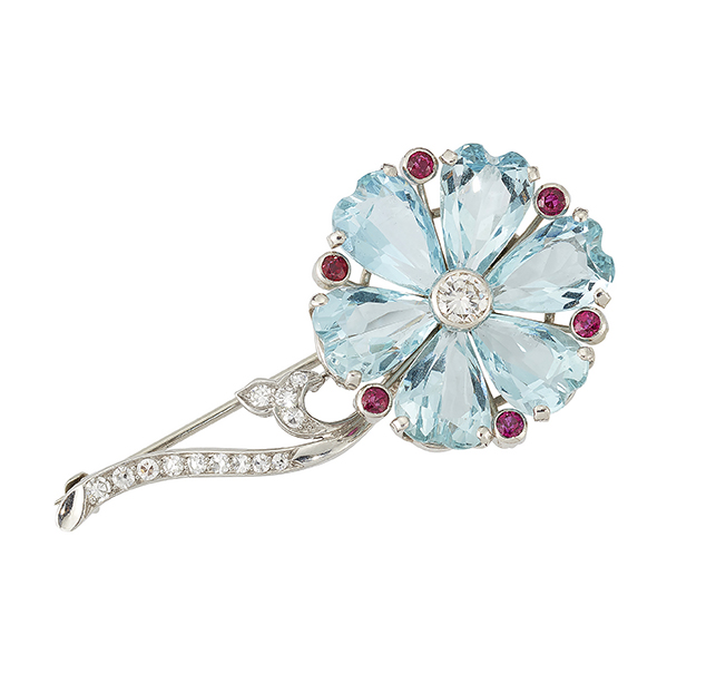 An aquamarine and diamond flower brooch, the flowerhead with claw-set faceted heart-shaped aquamarine petals with central circular-cut diamond and ruby single stone collet divisions to a graduated single-cut diamond stem and leaf detail, 5cm long