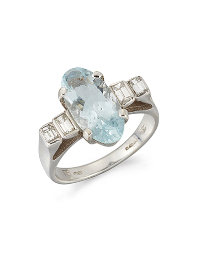 An 18ct. gold, aquamarine and diamond ring, the oval-cut aquamarine in claw-set mount with graduated rectangular-cut diamond two stone shoulders, in 18ct. white gold mount, London hallmarks, 2006, ring size M