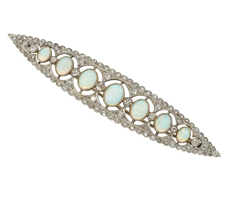 An Edwardian platinum, opal and diamond brooch, the navette shaped openwork panel set with seven oval graduated opals with old-brilliant-cut diamond trellis work detail, circa 1905, 8.5cm, in fitted case