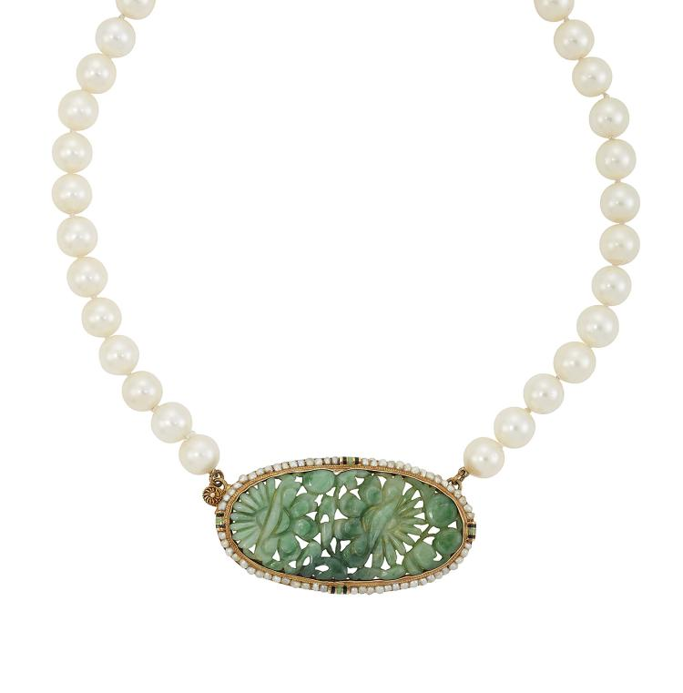 A cultured pearl necklace, composed of a single row of uniform cultured pearls approximate general diameter 7.0mm, to an early 20th century gold-mounted oval carved jadeite panel clasp with seed pearl border and enamel accents, 70cm long