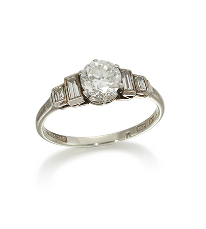 An Art Deco diamond single stone ring, the circular-cut diamond weighing 0.65 carats, in claw-set mount to baguette diamond two stone graduated stepped shoulders, ring size M1/2
