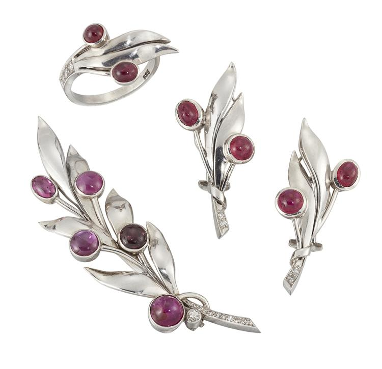 A suite of ruby jewellery, comprising: a brooch designed as a leaf frond set with five collet-set cabochon rubies and with single-cut diamond stem and circular-cut diamond single collet detail; and a pair of matching earclips and ring, ring size N