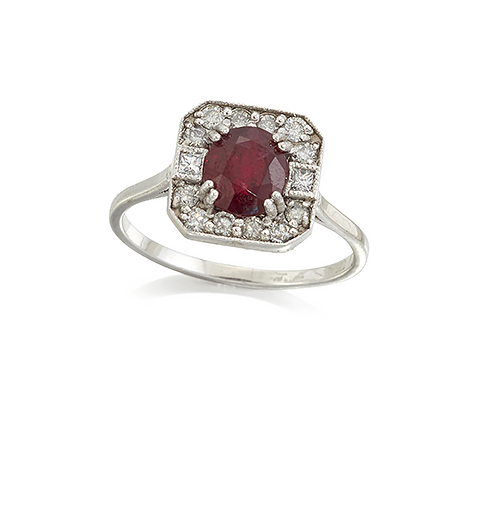 An 18ct. gold, ruby and diamond square cluster ring, the central oval-cut ruby in four double claw setting with circular-cut diamond border and princess-cut diamond single stone shoulders, ring size N