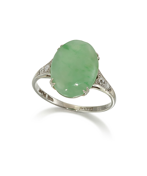 An Art Deco, jadeite and diamond ring, the oval cabochon jade in four claw platinum and white gold mount, to old brilliant-cut diamond shoulders, makers mark for Cornelius Desormeaux Saunders & James Frances (Frank) Hollings shepherd who are recorded as working from 1893 to 1929, ring size R1/2 (Please note that the jadeite has not been tested for natural colour origin)