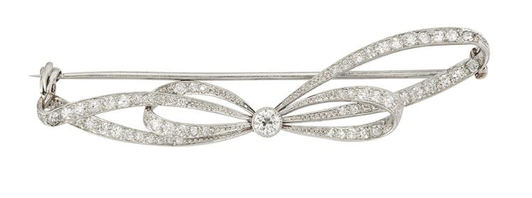A Belle Epoque platinum and diamond bow brooch, the old-brilliant-cut diamond loops with claw-set diamond single stone centre, circa 1915, French import mark to pin, 6.5cm wide