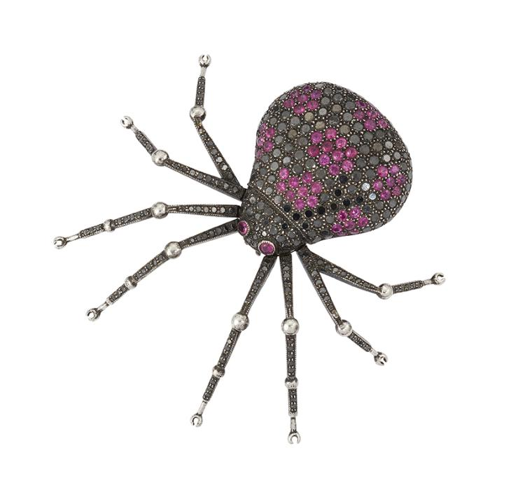 A diamond and ruby spider brooch, the body pave-set with circular-cut black diamonds and rubies in a reticulated pattern, with collet-set ruby single stone eyes, black diamond-set oxidised articulated legs with polished bead joints, 5.0cm long (Please note that the black diamonds have not been tested for natural colour origin)