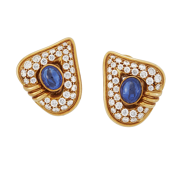 A pair of sapphire and diamond earclips, each designed as a leaf shaped pavé diamond panel with central collet-set cabochon sapphire, 2.5cm (2) Purportedly purchased from Chaumet by the current owner