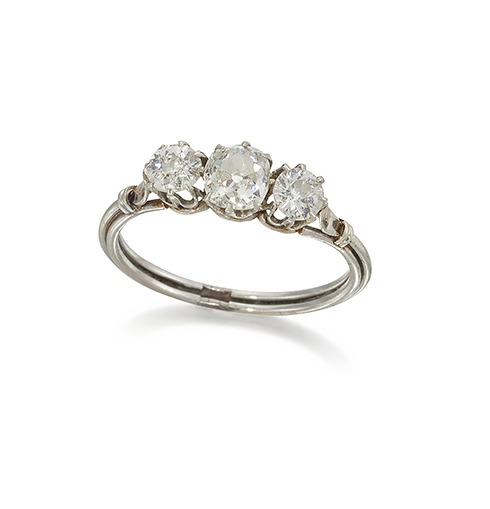 A diamond three stone ring, the central old-brilliant-cut diamond with diamond single stone shoulders to a reeded hoop, ring size M