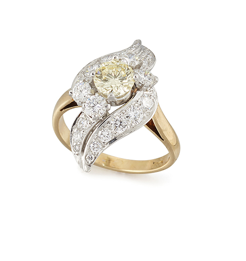 A diamond cluster ring, the central claw-set circular-cut fancy-pale yellow diamond with circular-cut diamond two stone shoulders and diamond leaf detail above and below, ring size N