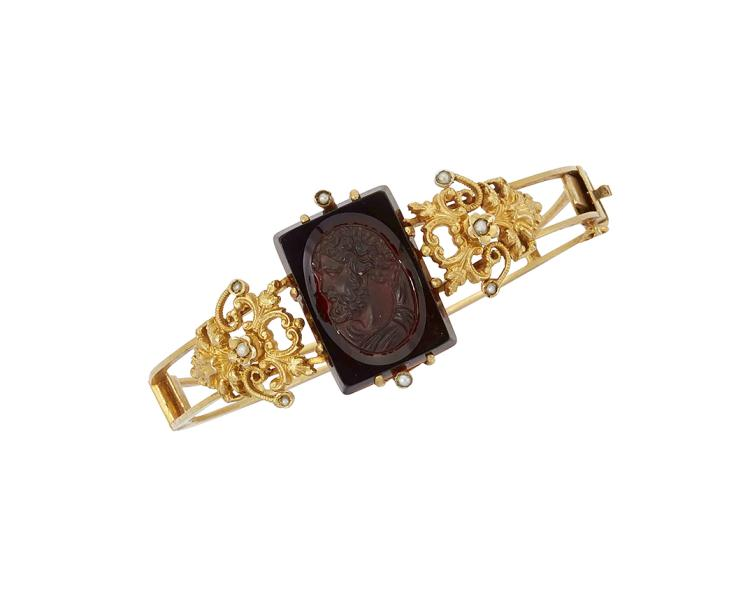 A late 19th century gilt bangle, the openwork hinged hoop with central square black glass cameo depicting the classical profile of a bearded man, with seed pearl set foliate panel shoulders, circa 1900, inner circumference 5.5cm, with fitted case