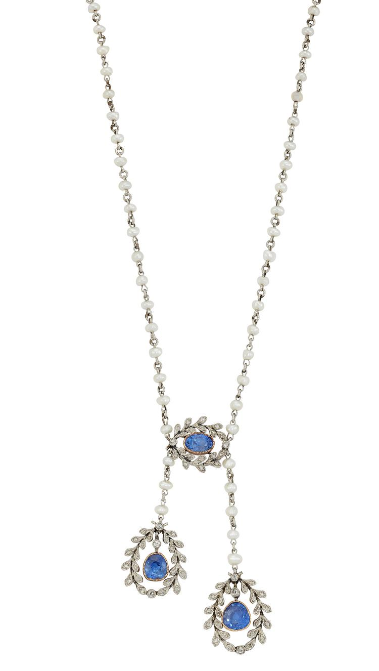 A charming Belle Epoque platinum, sapphire and diamond negligee necklace, composed of two gold millegrain-set cushion-cut sapphire drops with rose-cut diamond openwork garland borders suspended from a platinum and pearl chain-link necklace with central sapphire and diamond matching panel, circa 1910, 42cm long