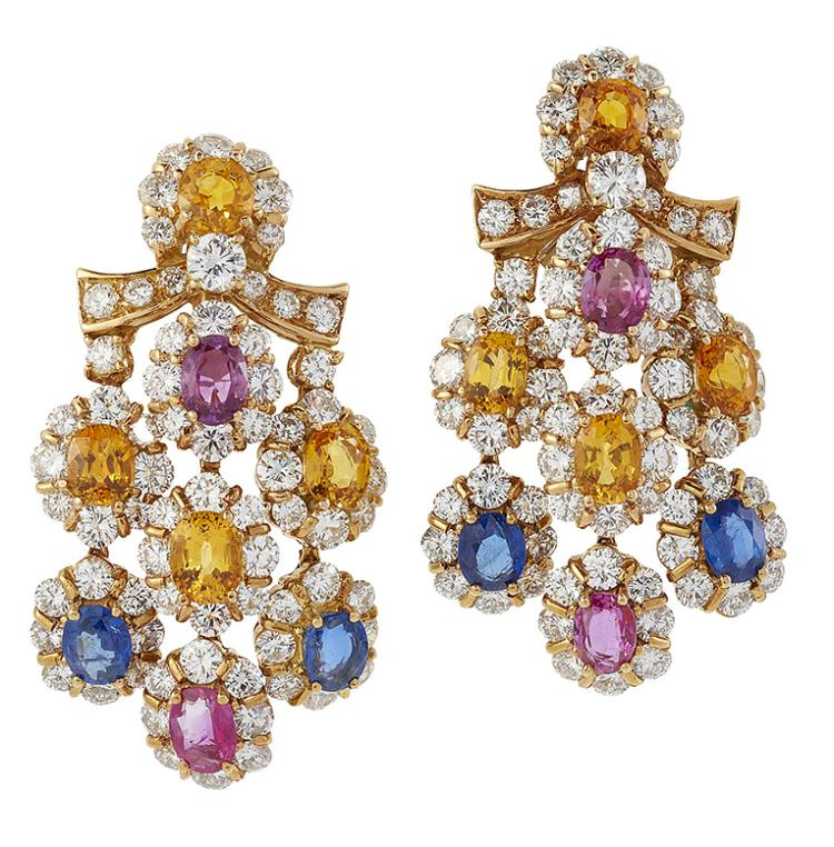 A pair of sapphire and diamond earpendants, each designed as a central oval yellow sapphire and circular-cut diamond cluster with diamond ribbon detail, suspending triple articulated drops the central drop composed of a two pink sapphire and diamond oval clusters and a central yellow sapphire and diamond cluster, the other two drops composed of alternate sapphire and diamond and yellow sapphire and diamond clusters, clip fittings, 5cm long